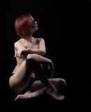 La femme nue de beauté s'asseyent sur le noir Photos stock