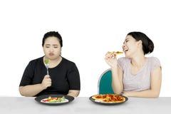 La femme obèse mangent de la salade et l'ami mangent de la pizza Photos stock