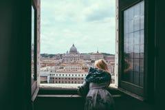 La femme observe de la fen?tre sur la basilique papale de St Peter images libres de droits