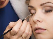 La femme obtenant des yeux composent fait par l'artiste photographie stock libre de droits