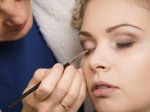La femme obtenant des yeux composent fait par l'artiste image stock