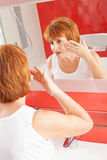 La femme obtient la crème sur le visage Photo stock