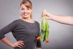 La femme obtient le bouquet des tulipes de l'homme Photographie stock libre de droits