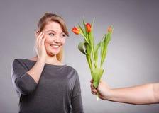 La femme obtient le bouquet des tulipes de l'homme Images stock