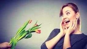 La femme obtient le bouquet des tulipes de l'homme Photo stock