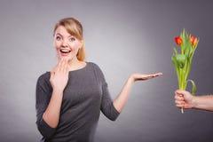 La femme obtient le bouquet des tulipes de l'homme Photos stock