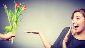 La femme obtient le bouquet des tulipes de l'homme Images libres de droits