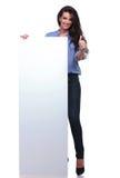 La femme occasionnelle avec le panneau montre le pouce  Photographie stock libre de droits