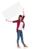 La femme occasionnelle de sourire tient l'affiche vide au-dessus de sa tête Photographie stock libre de droits