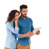 La femme occasionnelle se penchant sur le ` s de l'homme épaule pour lire sur le comprimé Image stock