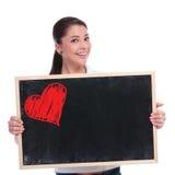 La femme occasionnelle tient le tableau noir avec le coeur Photo libre de droits
