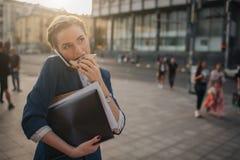 La femme occupée est pressé, elle n'a pas le temps, elle va manger le casse-croûte sur l'aller Travailleur mangeant, café potable image stock