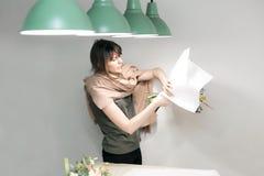 La femme ont le bouquet de fête de paquet en papier d'emballage Le jeune beau fleuriste rendent floristry pour se réunir avec la  Image stock