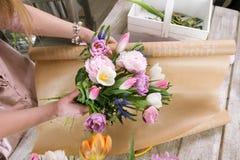 La femme ont le bouquet de tulipe de paquet en papier d'emballage Images stock