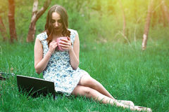 La femme ou la fille dans une robe, avec un ordinateur portable et des écouteurs, s'assied dessus Photos stock