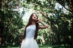 La femme ou la fille, une jeune mariée dans une robe de mariage blanche, se tient en m Images stock