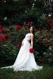 La femme ou une fille, une jeune mariée dans une robe blanche de mariage, se tient avec f Photographie stock