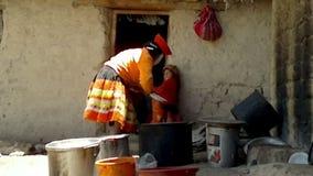 La femme péruvienne s'est habillée l'équipement fait main traditionnel coloré et en lavant un plat devant sa maison, Pata