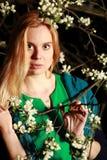 La femme par des fleurs sur l'arbre dans la nuit, portrait en gros plan, regarde u Photos libres de droits