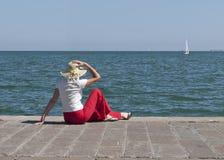 La femme par la mer observe le yacht en soleil Photo stock