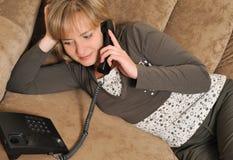 La femme parlant par le téléphone sur un sofa images libres de droits