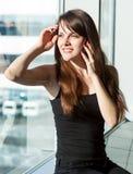 La femme parle au téléphone portable dans l'aéroport Image stock