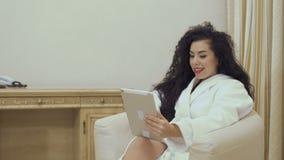 La femme parle avec des amis par l'appel visuel de la chambre d'hôtel banque de vidéos