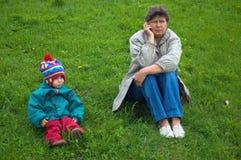 La femme parle du téléphone, la fille se repose ensuite Photo libre de droits