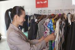 La femme passant par le dégagement vêtx au magasin de mode photo stock