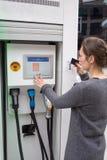 La femme paye à une station de charge de voiture électrique Photographie stock libre de droits