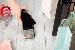 La femme paye avec la technologie de NFC sur un smartphone photos stock