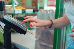 La femme paye des achats dans le magasin par la carte de crédit par le terminal de paiement photos stock