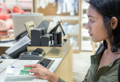 La femme paye le billet de banque dans le magasin Photographie stock libre de droits