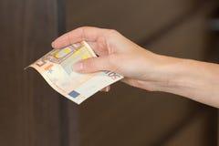 La femme paye le comptant le petit déjeuner dans le café avec d'euro billets de banque Photos stock