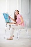 La femme peint le tableau sur la toile Photo stock