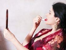 La femme peint ses languettes avec le rouge à lievres images stock