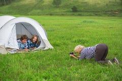 La femme photographie un garçon et une fille dans la tente de touristes Image libre de droits