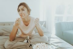 La femme pleurante seule mange du maïs éclaté sur le lit photos libres de droits