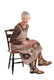 La femme plus âgée riante s'assied et se penche vers l'avant Photos stock