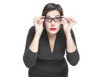 La femme plus de taille en verres regardant sur vous a isolé image stock