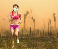 La femme portait un masque et un fonctionnement sur la pollution atmosphérique Images libres de droits