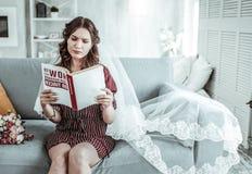 La femme portant un voile lit un livre photographie stock libre de droits