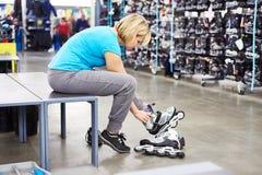 La femme porte des patins de rouleau dans la boutique de sports Photographie stock