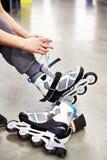 La femme porte des patins de rouleau dans la boutique de sports Photo libre de droits