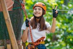 La femme porte le casque de protection apprécient des loisirs actifs en parc de corde photo libre de droits