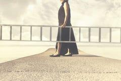 La femme porte une longue échelle pour s'élever dans le ciel images stock