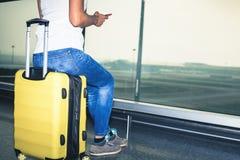 La femme porte votre bagage sur le terminal d'aéroport Photos stock