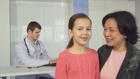 La femme pose avec sa fille à l'hôpital du ` s d'enfants banque de vidéos