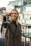 La femme positive gaie tient le verre de tige photographie stock