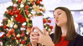 La femme près a décoré l'arbre de Noël Assez femelle utilisant le selfie faisant mobile, faisant les visages drôles clips vidéos
